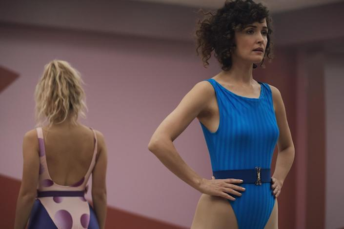 Rose Byrne in a leotard and a perm. Behind her is another woman in a leotard.