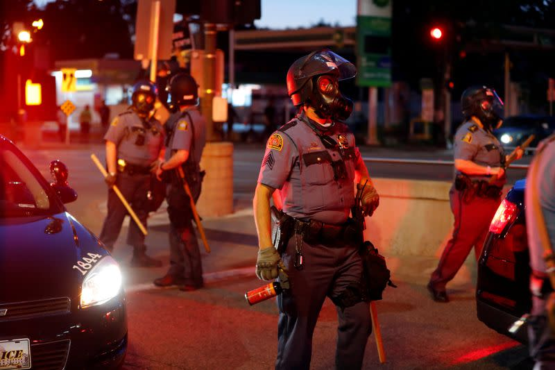 Police officers face protesters after a white police officer was caught on a bystander's video pressing his knee into the neck of African-American man George Floyd, who later died at a hospital, in St. Paul