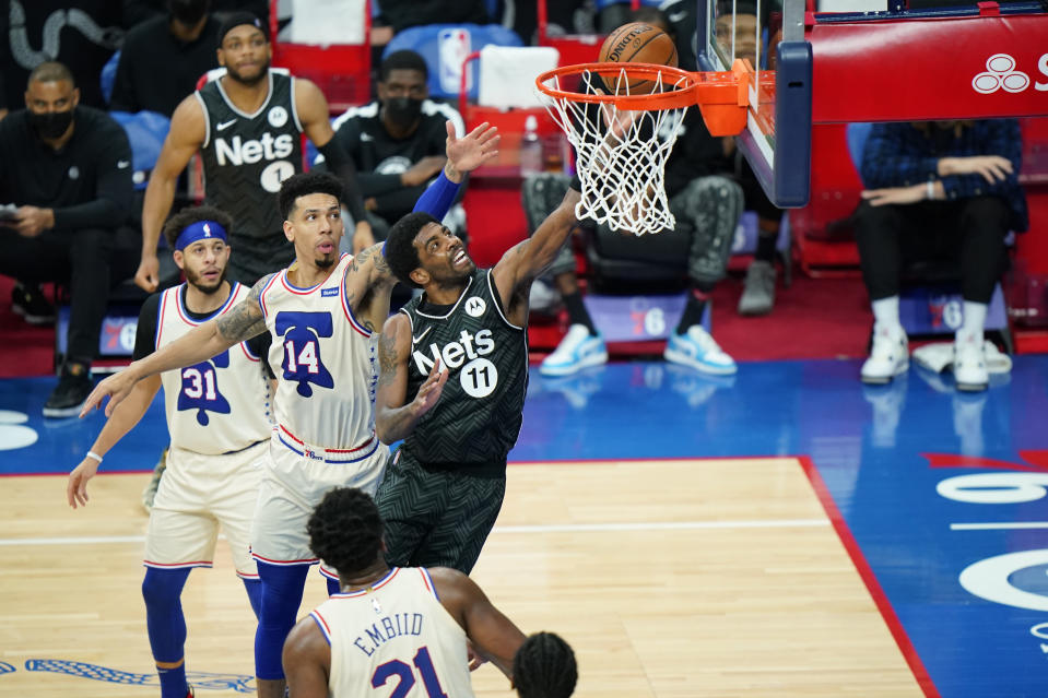 Brooklyn Nets' Kyrie Irving (11) goes up for a shot against Philadelphia 76ers' Danny Green (14) and Seth Curry (31) during the first half of an NBA basketball game, Wednesday, April 14, 2021, in Philadelphia. (AP Photo/Matt Slocum)