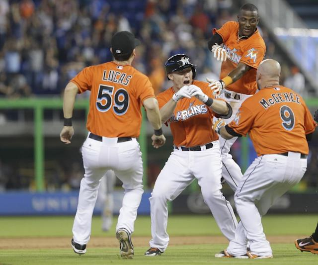 Miami Marlins' Jeff Baker, second from left, is mobbed by teammates after hitting a double that scored Adeiny Hechavarria, second from right, during the ninth inning of a baseball game against the Los Angeles Dodgers, Sunday, May 4, 2014 in Miami. The Marlins defeated the Dodgers 5-4. Ed Lucas (59) and Casey McGehee (9) are shown. (AP Photo/Wilfredo Lee)