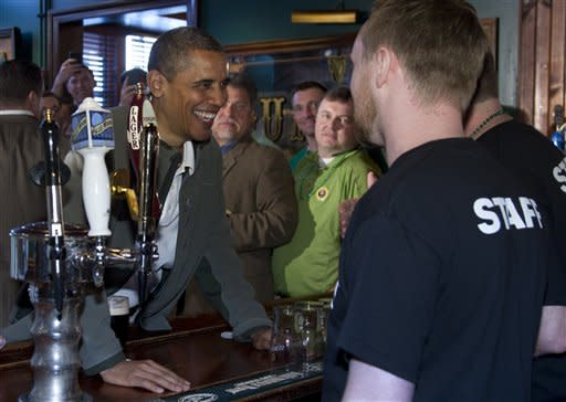 President Barack Obama, left, talks with staff behind the bar at The Dubliner Restaurant and Pub and Restaurant on St. Patrick's Day, Saturday, March 17, 2012, in Washington. (AP Photo/Carolyn Kaster)