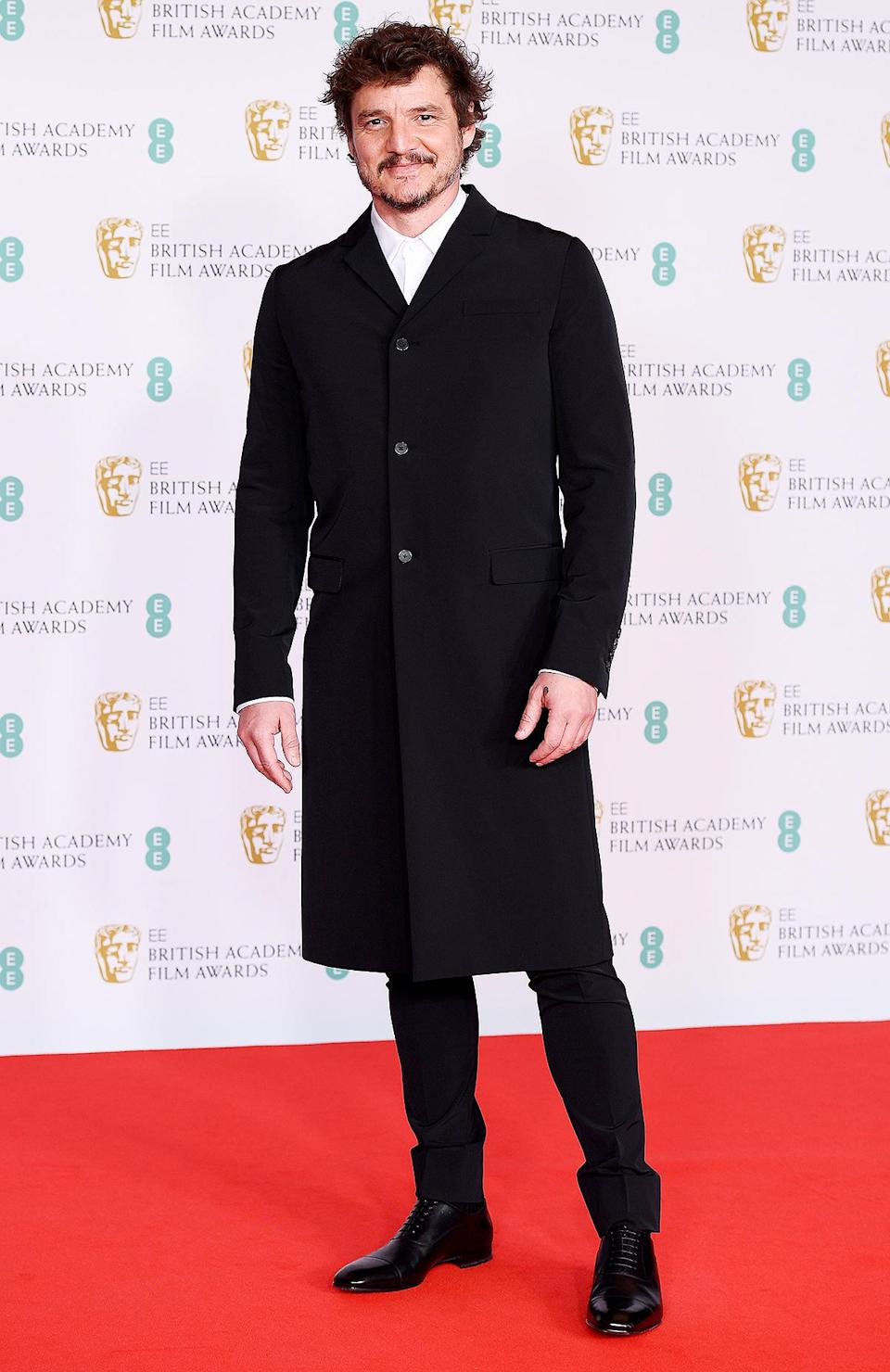 <p>in a single-breasted coat, black trousers, white shirt and derby shoes, all by Prada.</p>