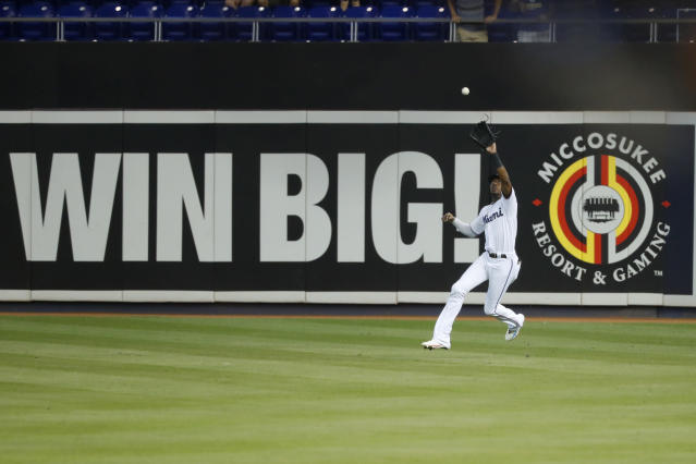 Miami Marlins center fielder Lewis Brinson catches a sacrifice fly by Milwaukee Brewers' Mike Moustakas during the first inning of a baseball game, Thursday, Sept. 12, 2019, in Miami. Lorenzo Cain scored on the play. (AP Photo/Wilfredo Lee)