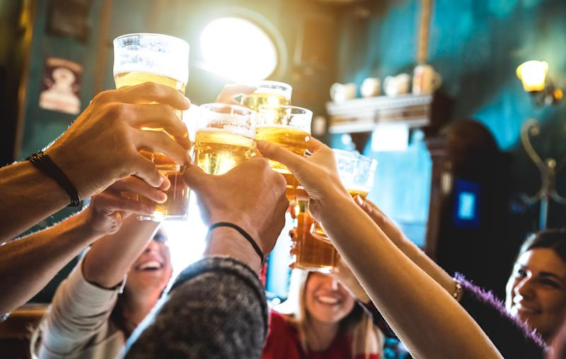 A group of happy friends drinking and toasting beer at a pub.