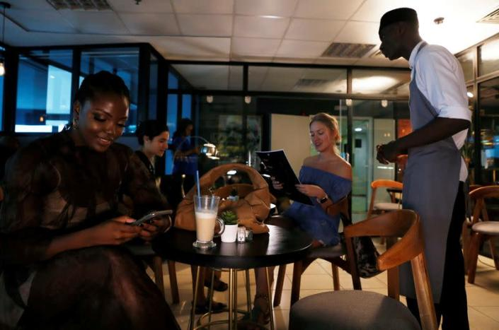 A waiter attends to customers at Mai Shayi cafe in Victoria Island, Lagos