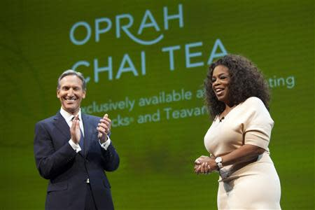 Howard Schultz (L), CEO of Starbucks, announces the new Teavana Oprah Chai Tea with Oprah Winfrey during the company's annual shareholders meeting in Seattle, Washington March 19, 2014. REUTERS/David Ryder