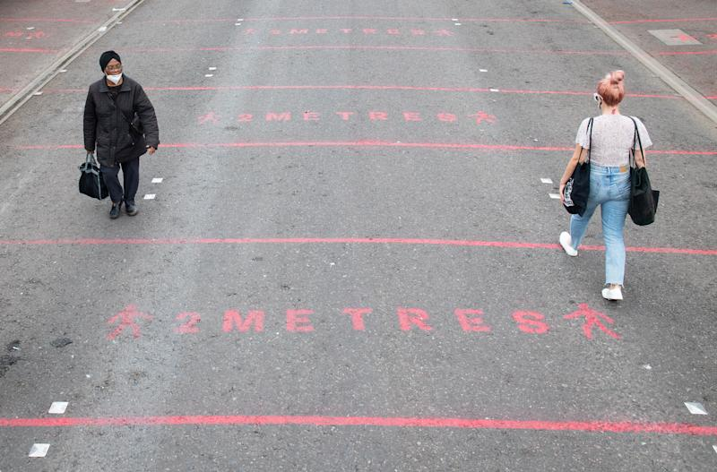 "People walk over two metre social distancing markings at Ridley Road street market in east London, as the government considers relaxing official guidelines on social distancing to a shorter distance of one metre. Health Secretary Matt Hancock, pressed to reduce social distancing from two metres to one metre, has told the Commons: ""It's the sort of thing of course we want to lift and we need to do that in a way that is careful and safe."