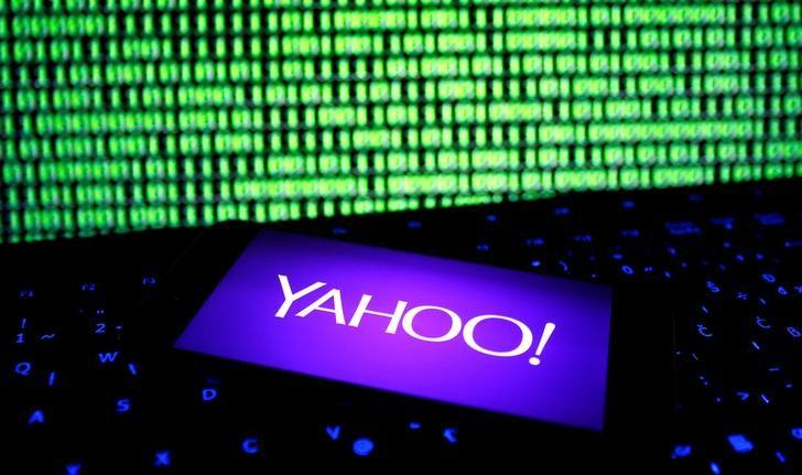 A photo illustration shows a Yahoo logo on smartphone in front of a displayed cyber code and keyboard