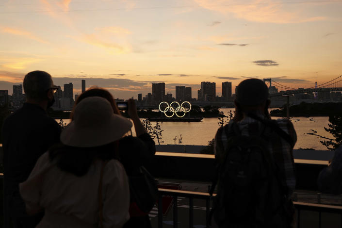 People take photos of the Olympic Rings displayed by the Odaiba Marine Park Olympic venue ahead of the Tokyo 2020 Olympic Games on July 19, 2021. (Toru Hanai / Getty Images)