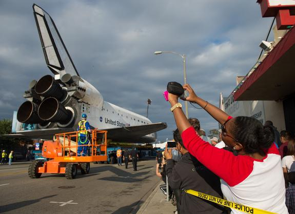 Spectators are seen photographing space shuttle Endeavour as it passes by on its way to its new home at the California Science Center, Friday, Oct. 12, 2012, in Inglewood.