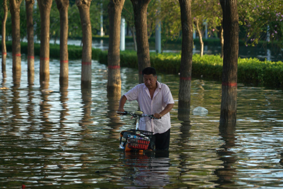 A man pushes a scooter through floodwaters in Xinxiang in central China's Henan Province, Monday, July 26, 2021. Forecasters Monday said more heavy rain is expected in central China's flood-ravaged Henan province, where the death toll continues to rise after flash floods last week that killed dozens of people. (AP Photo/Dake Kang)