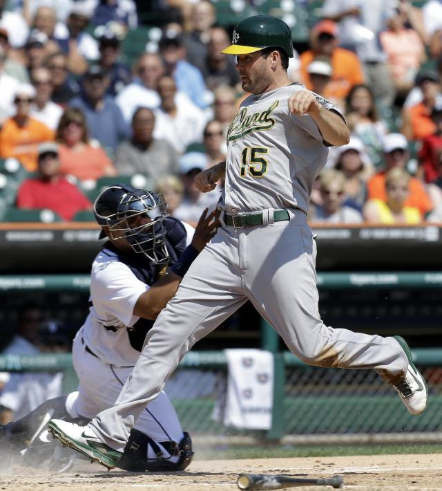 Oakland Athletics' Seth Smith (15) scores on a sacrifice fly by Eric Sogard as Detroit Tigers catcher Brayan Pena (55) tries to make the tag in the fourth inning of a baseball game in Detroit, Thursday, Aug. 29, 2013. (AP Photo/Paul Sancya)