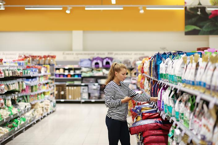 Woman shopping in supermarket reading product information. Pet food.