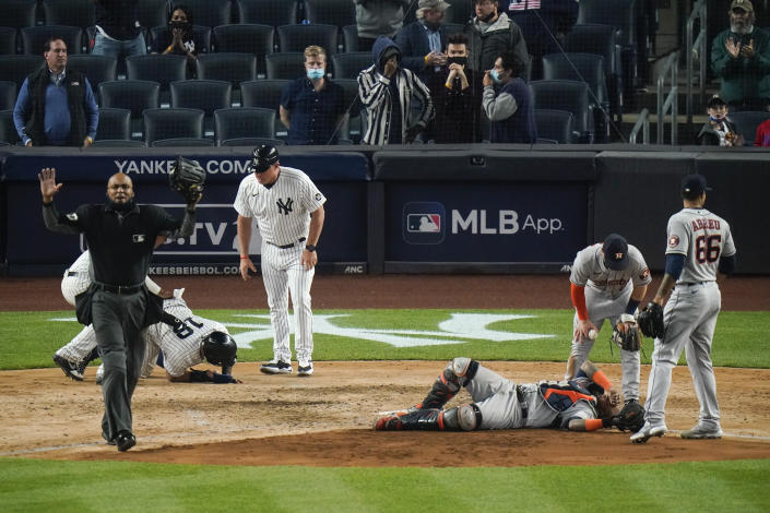 Players gather around New York Yankees' Rougned Odor (18) and Houston Astros catcher Martin Maldonado after they were injured during the sixth inning of a baseball game Tuesday, May 4, 2021, in New York. (AP Photo/Frank Franklin II)