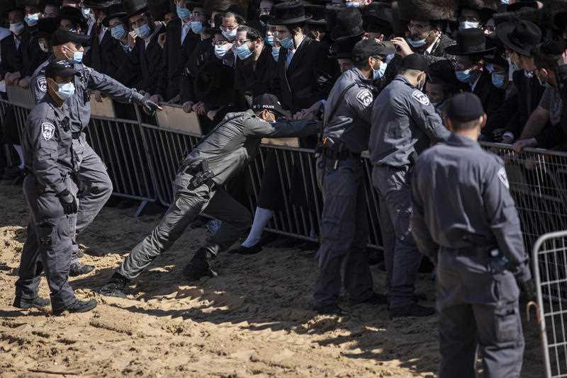 Israeli police try to control a crowd of mourners during the funeral of Rabbi Mordechai Leifer, the latest in a string of clashes between security forces and ultra-Orthodox Jews violating a national coronavirus lockdown order, in the port city of Ashdod, Israel.