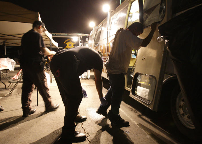 Maricopa County sheriff's deputies check the shoes of a suspect arrested during a crime suppression sweep in Phoenix on Thursday, July 29, 2010.(Photo: Ross D. Franklin/AP)