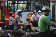 People wear face masks in hopes of curbing the spread of the coronavirus riding mopeds in Hanoi, Vietnam on Thursday, Aug. 6, 2020. Vietnamese health official said on Thursday the COVID-19 outbreak would peak in the coming ten days as the country reported another death and a score of new infections. (AP Photo/Hau Dinh)