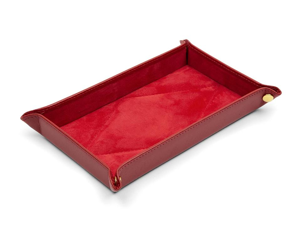 """<p>Get your dressing table organized with a little inspiration from Queen Elizabeth with this red leather trinket tray from the iconic British brand, Launer. The Queen has been carrying their handbags for over five decades with some of her favorite styles recently making their debut on Netflix's <em>The Crown</em>.</p> <p><strong>Buy it! Launer Angelo Tray, $179; <a href=""""https://shop.launer.com/p/938-02"""" rel=""""nofollow noopener"""" target=""""_blank"""" data-ylk=""""slk:shop.launer.com"""" class=""""link rapid-noclick-resp"""">shop.launer.com</a></strong></p>"""