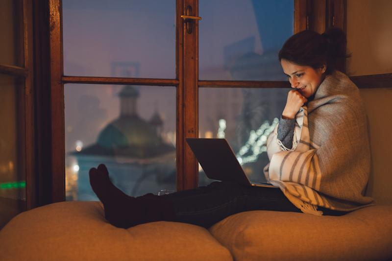 Relaxed woman at the window sill enjoying a movie on the lap top