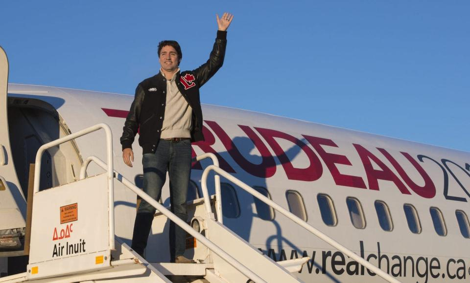Trudeau waves as he steps off his campaign plane.