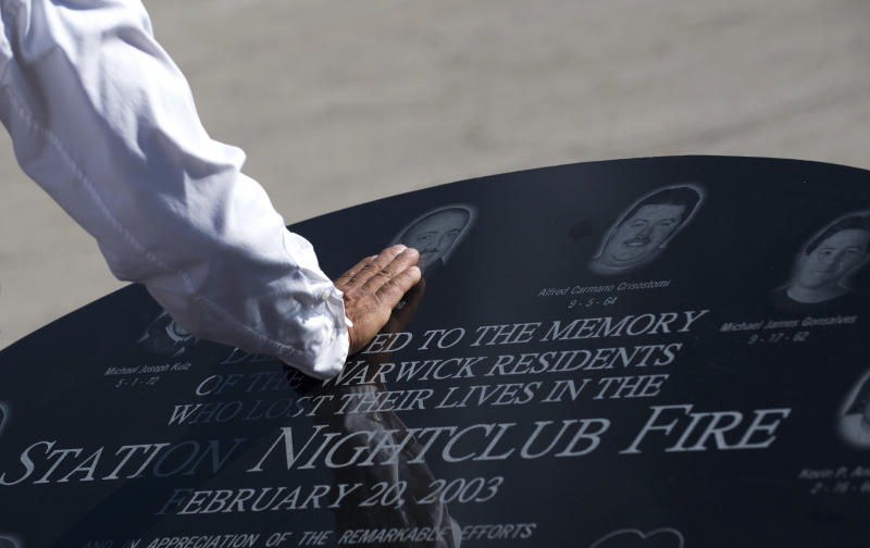 FILE - In this Oct. 20, 2012 file photo, Jody King touches the image of his brother Tracy King following a ceremony in Warwick, R.I. held to unveil a memorial stone that honors victims of The Station nightclub fire in West Warwick, where 100 were killed on Feb. 20, 2003. Ten years later, the imprint of the fire remains - including in the state's strict fire code, passed soon after the blaze, that requires all nightclubs like The Station to install sprinklers. (AP Photo/Gretchen Ertl, File)