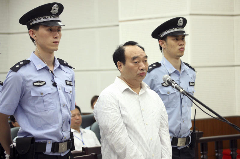 In this  June 19, 2013 photo, Lei Zhengfu, center, former Communist Party chief of Beibei district, who was involved in a sex tape scandal, attends his trial on corruption charges,  in a court in southwest China's Chongqing Municipality. While the corruption trials of high-level officials typically look like the scripted outcome of behind-the-scenes bargaining, this case offers a rare look at what happens when a lower-level official is caught in a high-profile crackdown with few political cards to play.  (AP Photo) CHINA OUT