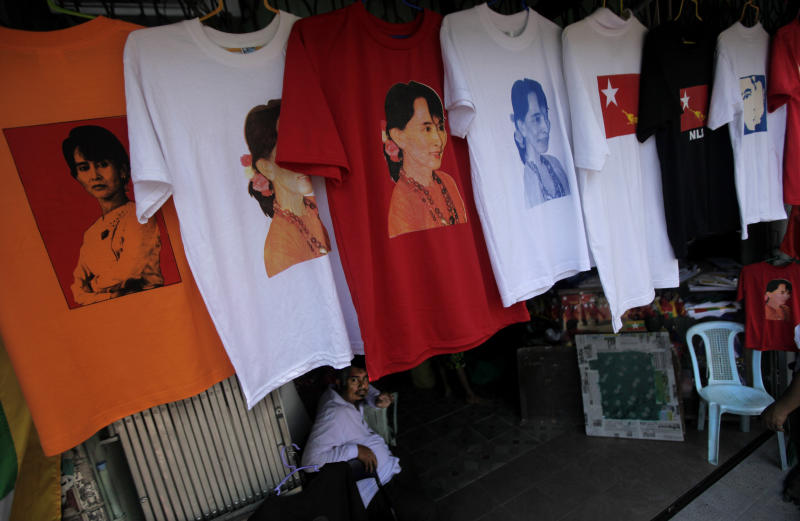 """In this photo taken, Thursday, Feb 23, 2012, T-shirts, with the photographs of Myanmar's pro-democracy icon Aung San Suu Kyi printed on them, are displayed for sale at a shop in Yangon, Myanmar. Suu Kyi's once-banished image now appears everywhere, on T-shirts, keychains and coffee mugs. Pirated copies of """"The Lady"""", the big screen version of Suu Kyi's life, are the best-selling DVD on Yangon streets. (AP Photo/Altaf Qadri)"""