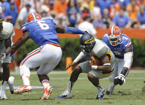 Toledo quarterback Terrance Owens, center, can't find room to run as he is caught between Florida defensive end Dante Fowler Jr. (6) and defensive lineman Dominique Easley (2) in the first half of an NCAA college football game, Saturday, Aug. 31, 2013, in Gainesville, Fla. (AP Photo/John Raoux)