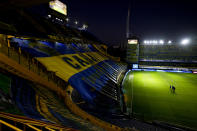 Soccer players walk on the field of the empty Bombonera stadium prior to a match between Boca Juniors and Racing Club in Buenos Aires, Argentina, Monday, Aug. 30, 2021. All that soccer fans have been allowed to do during the pandemic is to enter stadiums several hours before a match and drape flags over the stands where they used to cheer. (AP Photo/Natacha Pisarenko)