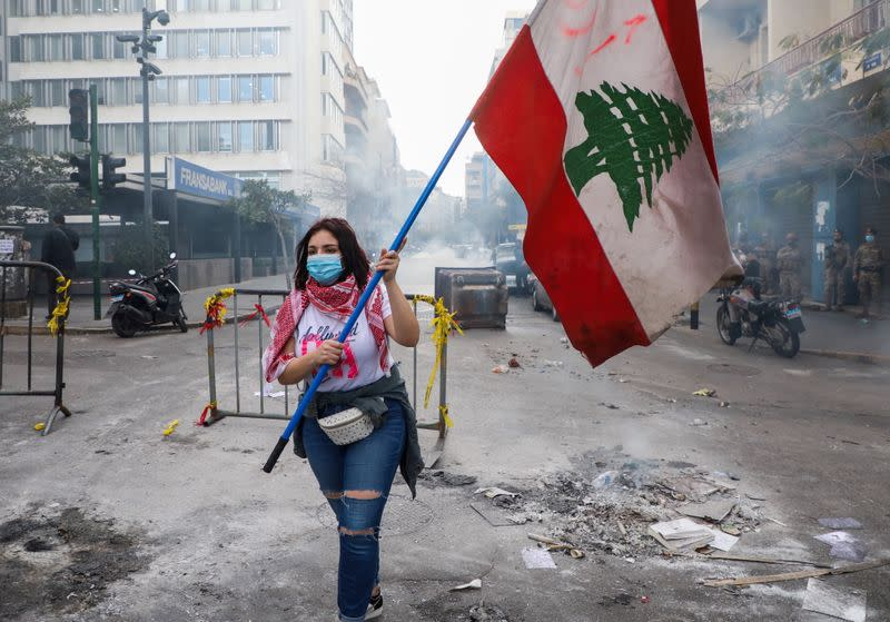 FILE PHOTO: A demonstrator carries a national flag during a protest in Beirut