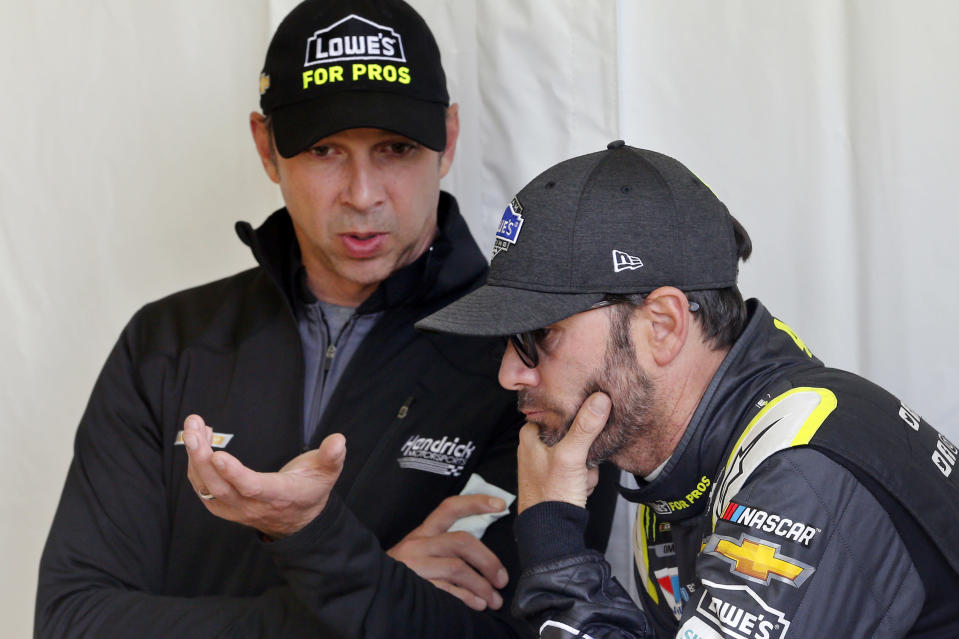 FILE - In this Friday, April 20, 2018, file photo, Jimmie Johnson, right, listens to crew chief Chad Knaus, as they wait for their car to get through inspection prior to qualifying for the NASCAR Cup Series auto race at Richmond Raceway in Richmond, Va. Johnson is retiring from full-time NASCAR competition in Sunday's season finale at Phoenix Raceway, leaving the sport as a seven-time champion ranked sixth on the all-time wins list with 83 career victories. (AP Photo/Steve Helber, FIle)