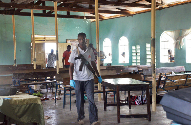 An armed Kenyan policeman walks inside the African Inland Church, as a body of one of those killed in the attack lies on the ground underneath church pews, in Garissa, Kenya Sunday, July 1, 2012. Grenade and gunfire attacks on two Kenyan churches near the border with Somalia killed 10 people and wounded 40 on Sunday in what was likely an attack by militants from Somalia, an official said. (AP Photo/Chris Mann)