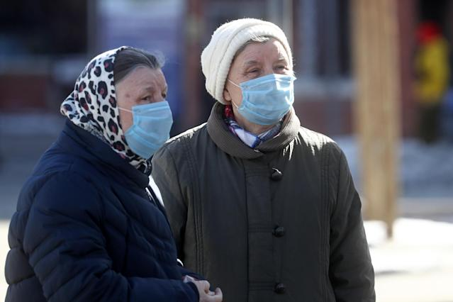 Two elderly women wearing medical masks in a street in Moscow as Europe has become the centre of the coronavirus outbreak. (Getty)