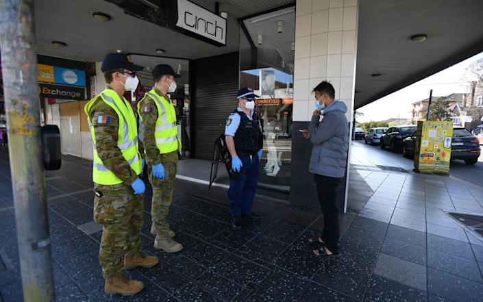 NSW Police and Defence Force members speak to a man about compliance at Campsie in Sydney - JOEL CARRETT/EPA-EFE/Shutterstock