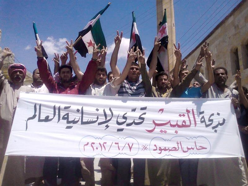 "In this citizen journalism image provided by Edlib News Network ENN, anti-Syrian regime protesters chant slogans and hold a banner in Arabic that reads, ""Al-Qubair massacre challenges the world's humanity,"" during a protest against the massacre of Mazraat al-Qubair, in the northern village of Hass, in Idlib province, Syria, Thursday June 7, 2012. Syria on Thursday denied as ""absolutely baseless"" claims by opposition groups about a new massacre in the central Hama province in which government forces allegedly killed dozens of people, including women and children. (AP Photo/Edlib News Network ENN) THE ASSOCIATED PRESS IS UNABLE TO INDEPENDENTLY VERIFY THE AUTHENTICITY, CONTENT, LOCATION OR DATE OF THIS HANDOUT PHOTO"