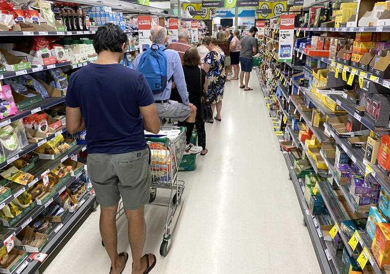 People are seen lined up waiting to go through the checkout inside Woolworths at Mt Gravatt in Brisbane.