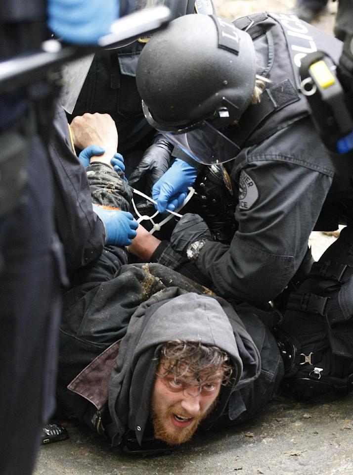 "Police officers arrest a protester in the Portland encampment Sunday, Nov. 13, 2011, in, Portland, Ore. In a tense escalation of the Occupy Portland protest, police in riot gear Sunday surrounded demonstrators in a downtown park area after hundreds of people defied the mayor's order to leave the park by midnight. By early afternoon, officers had mostly surrounded the camp where the protesters were holding a ""general assembly"" meeting to discuss their next moves following the eviction order. (AP Photo/Rick Bowmer)"