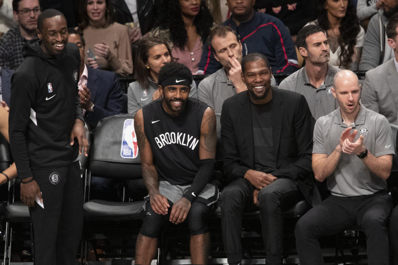 Brooklyn Nets guard Theo Pinson, left, guard Kyrie Irving, center and forward Kevin Durant watch the game action during the second half of an NBA basketball game against the Houston Rockets, Friday, Nov. 1, 2019, in New York. The Nets won 123-116. (AP Photo/Mary Altaffer)
