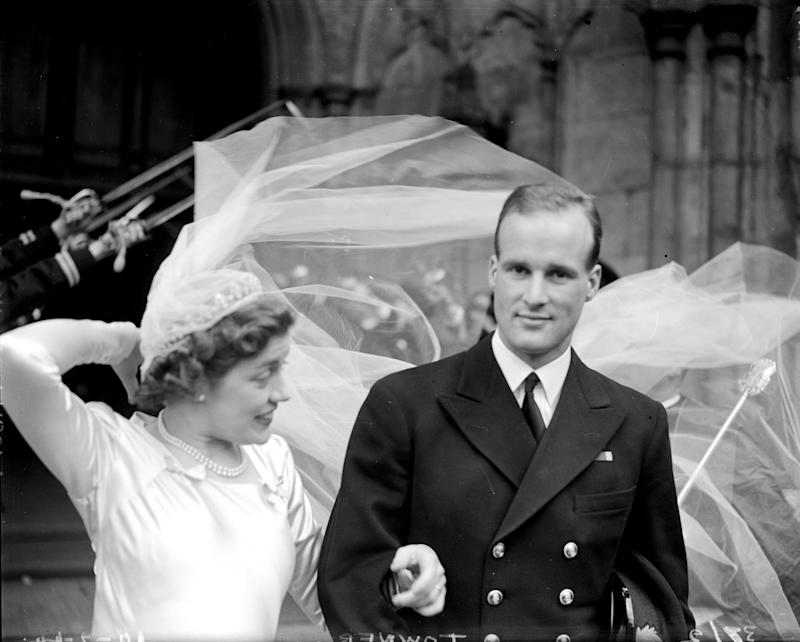 Lady Anne Spencer struggles to control her veil as she and her new husband Lt Christopher Wake-Walker leave Westminster Abbey, London, after their wedding on February 10, 1944.