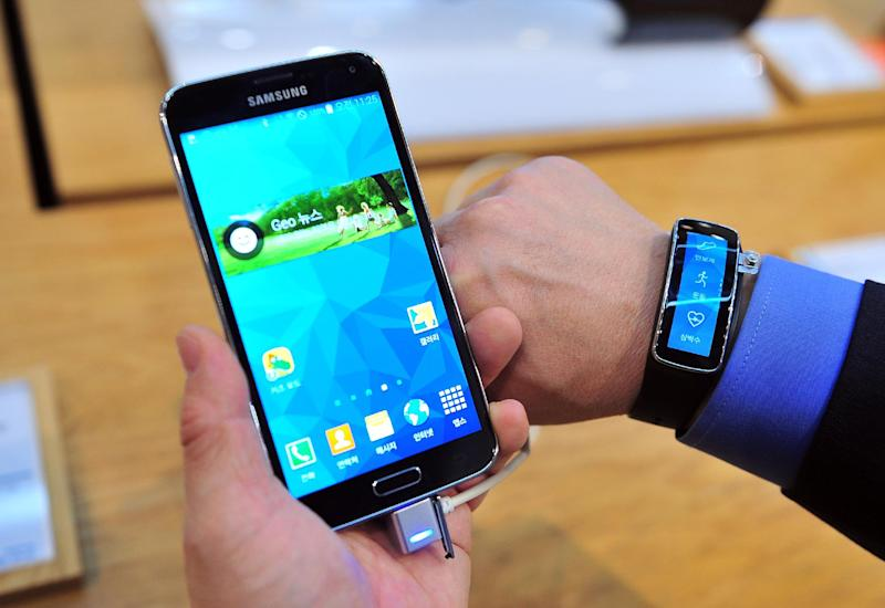 A visitor checks out a Samsung Galaxy S5 smartphone, at a showroom in Seoul, on April 29, 2014
