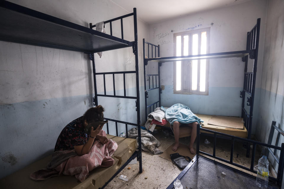 Minors who crossed into Spain take shelter inside an abandoned building in Ceuta, Friday, May 21, 2021. Spain says it has returned to Morocco over 6,600 of the more than 8,000 migrants who swam or jumped over border fences into one of Spain's enclaves in North Africa this week. Social services in Ceuta were dealing with thousands of calls from Moroccan parents looking for their children and trying to speed up family reunions, said authorities in Spain's north African enclave at the heart of a sudden humanitarian crisis and a diplomatic storm with Morocco. (AP Photo/Bernat Armangue)