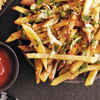"""<p>Tossing the fries in a small amount of butter and garlic after cooking makes them unbelievably rich, yet still lower in fat than <a href=""""https://www.myrecipes.com/how-to/cooking-questions/who-invented-french-fries"""" rel=""""nofollow noopener"""" target=""""_blank"""" data-ylk=""""slk:fast-food fries"""" class=""""link rapid-noclick-resp"""">fast-food fries</a>.</p>"""