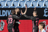 Real Madrid's Karim Benzema, 2nd left, celebrates with Ferland Mendy, left and Lucas Vazquez after scoring his side's second goal during a Spanish La Liga soccer match between Celta and Real Madrid at the Balaidos stadium in Vigo, Spain, Saturday March 20, 2021. (AP Photo/Lalo R.Villar)