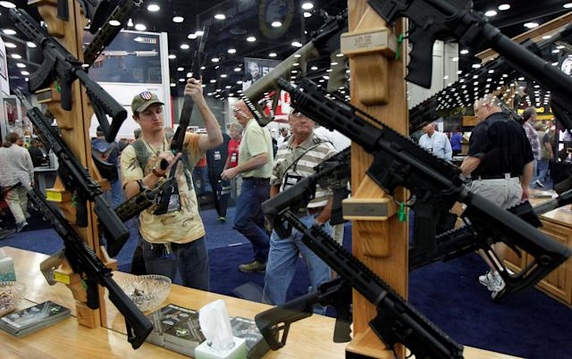 Gun enthusiasts look over Rock River Arms' guns at the National Rifle Association's annual meetings and exhibits show in Louisville, Kentucky, on May 21, 2016.