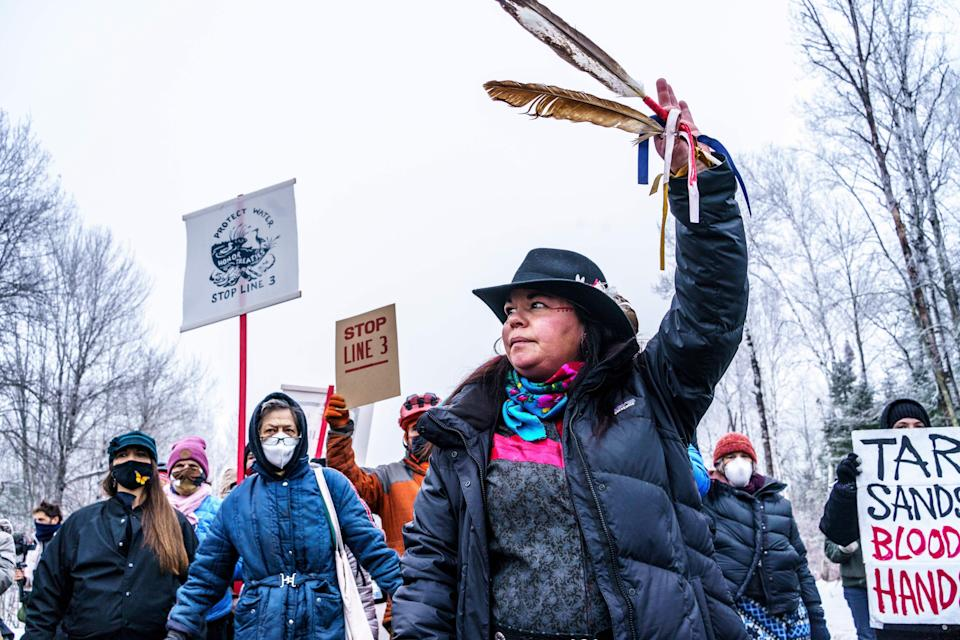 A Native American environmental activist dances with an eagle feather in front of the construction site for Enbridge's Line 3 oil pipeline near Palisade, Minnesota on January 9, 2021. (Photo: Kerem Yucel/AFP/Getty Images)