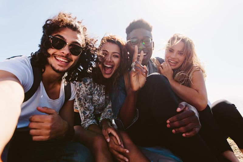 Excited young friends taking selfie outdoors. Diverse group of men and women sitting together and taking self portrait on their holiday.