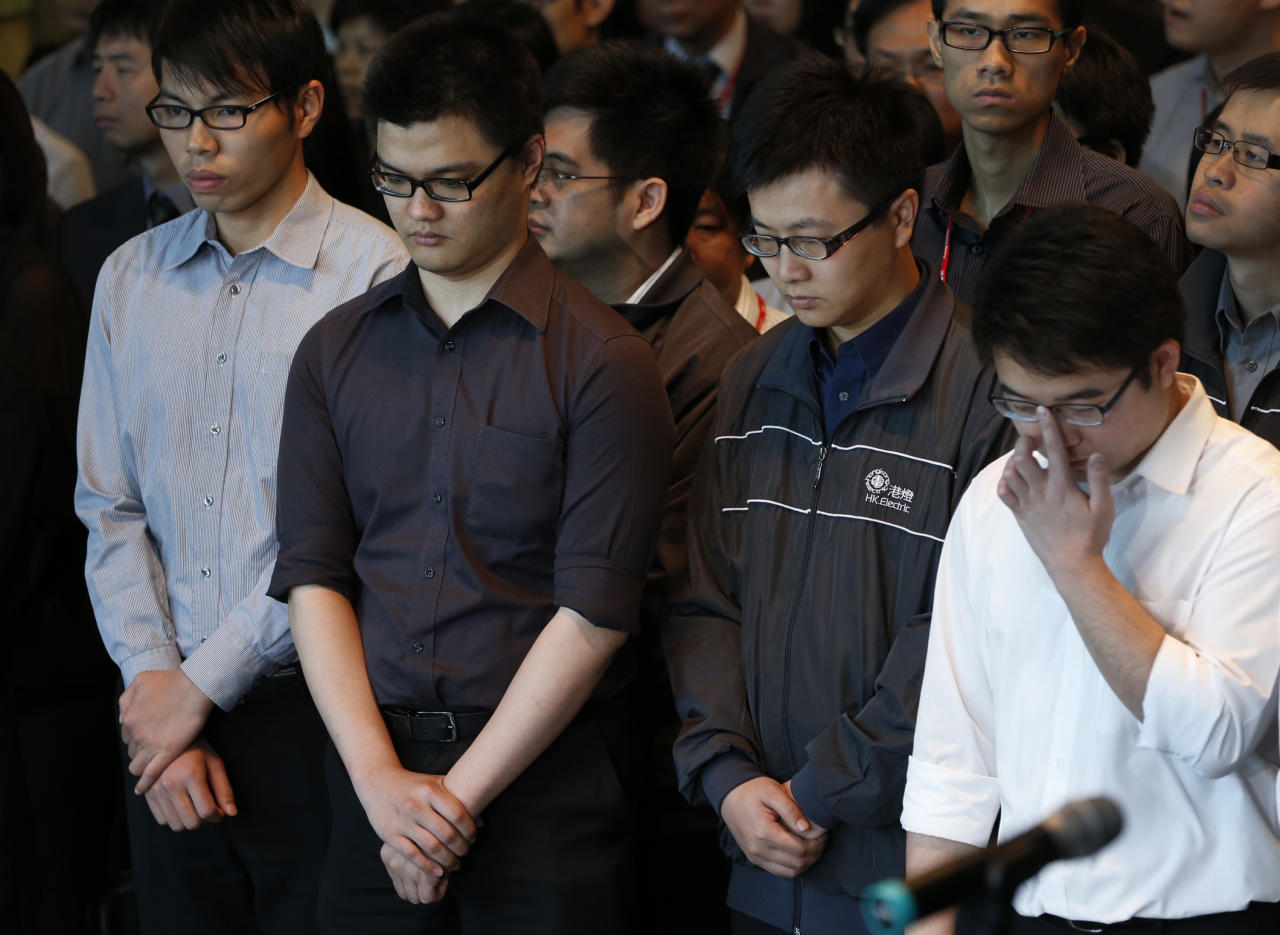 Staff members of Hong Kong Electric Co. pay tribute to victims who were killed in a ferry collision in Hong Kong Thursday, Oct. 4, 2012, as three days of mourning begin across the territory. All 38 people killed had been on the Lamma IV, owned by utility company Hong Kong Electric, which was taking about 120 of its workers and their families to watch fireworks in celebration of China's National Day and mid-autumn festival. (AP Photo/Vincent Yu)