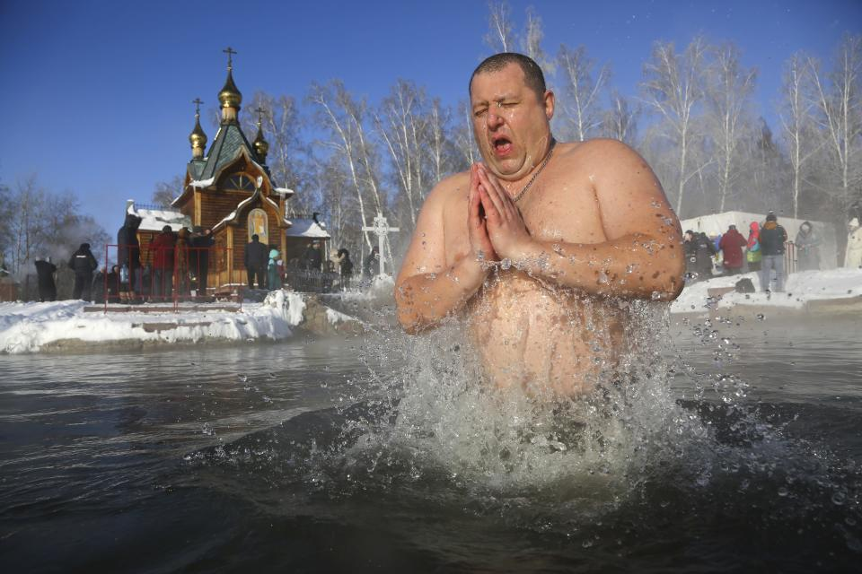 A man bathes in water during a traditional Epiphany celebration as the temperature dropped to about -24 degrees (-11,2 degrees Fahrenheit) near the Achairsky monastery outside Siberian city of Omsk, Russia, Tuesday, Jan. 19, 2021. Water that is blessed by a cleric on Epiphany is considered holy and pure until next year's celebration, and is believed to have special powers of protection and healing. The Russian Orthodox Church follows the old Julian calendar, according to which Epiphany falls on Jan. 19. (AP Photo/Evgeniy Sofiychuk)