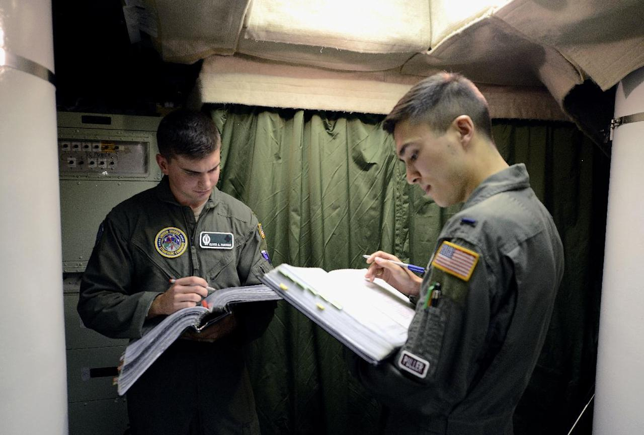 ** FOR TRANSMISSION AFTER 1AM, WEDNESDAY, JULY 9, 2014 ** In this photo taken June 24, 2014, 2nd Lt. Oliver Parsons, left, and 1st Lt. Andy Parthum go through a checklist in the underground control room where they work a 24-hour shift at an ICBM launch control facility near Minot, N.D. The crew is responsible for controlling and launching the 10 nuclear-tipped Minuteman 3 missiles located in remote launch sites under their command. (AP Photo/Charlie Riedel)