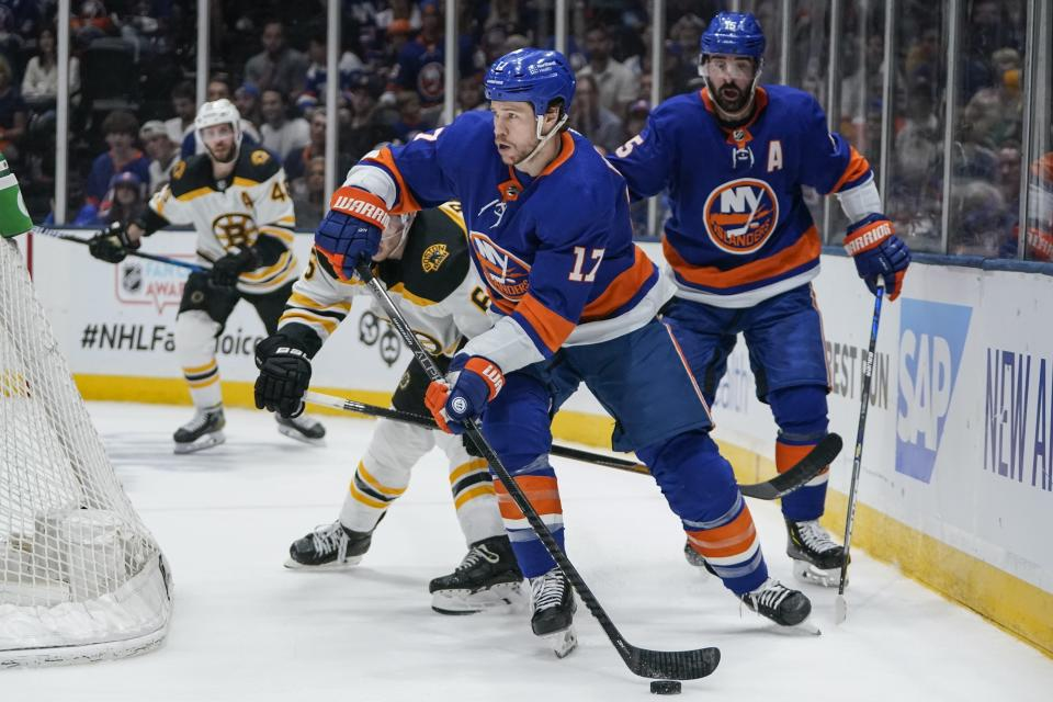 New York Islanders' Matt Martin (17) looks to pass the puck away from Boston Bruins' Mike Reilly (6) during the second period of Game 4 during an NHL hockey second-round playoff series Saturday, June 5, 2021, in Uniondale, N.Y. (AP Photo/Frank Franklin II)